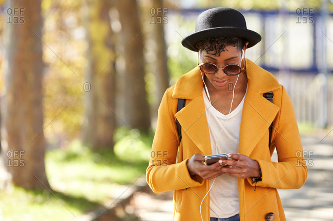 Fashionable young woman wearing a hat, sunglasses and a yellow pea coat standing on a tree lined street using her smartphone, close up