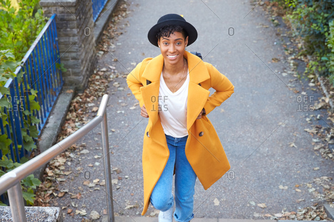 Elevated view of fashionable woman wearing a hat and a yellow pea coat and blue jeans walking up street stairs smiling to camera, close up