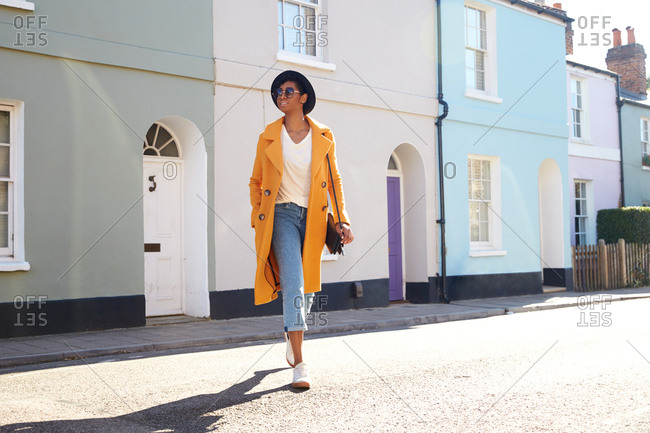Low angle view of fashionable young woman wearing an unbuttoned yellow pea coat and rolled up blue jeans walking in a street of terraced houses, backlit