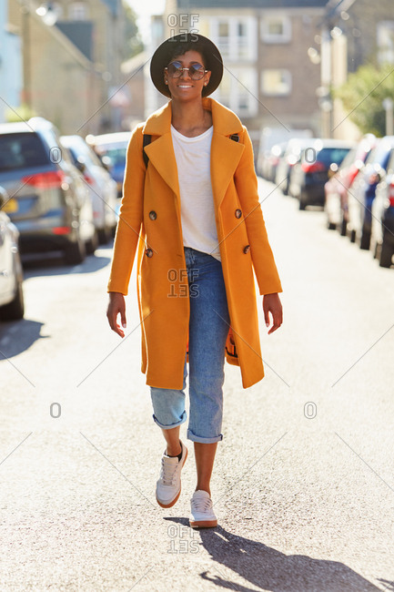 Fashionable young woman wearing blue jeans and an unbuttoned yellow pea coat walking in a road between parked cars, smiling on a sunny day, full length, backlit