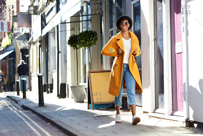 Fashionable young woman wearing blue jeans and an unbuttoned yellow pea coat walking on pavement near shops on a sunny day, low angle