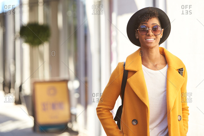 Young woman wearing a black hat and a yellow pea coat walking in a city street smiling to camera, close up