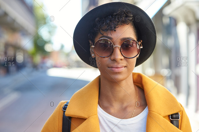 Head and shoulders portrait of young woman wearing black homburg hat and sunglasses standing on the street looking to camera, front view