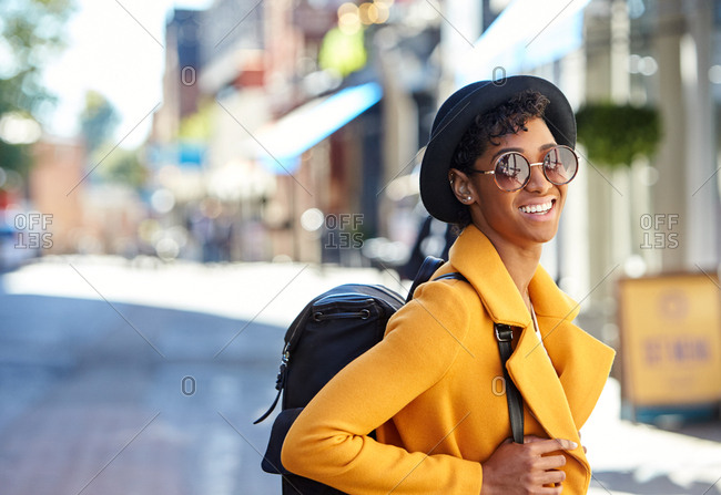 Close up of young woman wearing black homburg hat,  sunglasses, yellow coat and a backpack standing on a city street smiling to camera, waist up, side view