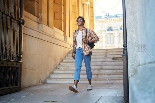 Low angle view of young woman a wearing plaid shirt, sunglasses and rolled up blue jeans walking through the gateway of a historical building, selective focus
