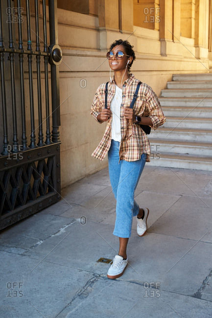 Front view of a young woman wearing a plaid shirt, sunglasses and rolled up blue jeans walking through the gateway of a historical building, using earphones, vertical