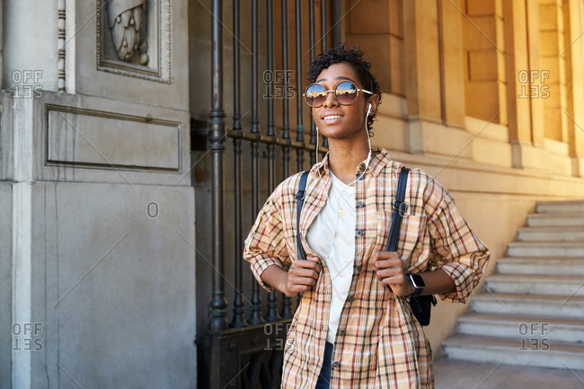 Close up of a young woman wearing sunglasses and a plaid shirt standing on the street outside the gateway of a historical building smiling and using earphones, front view
