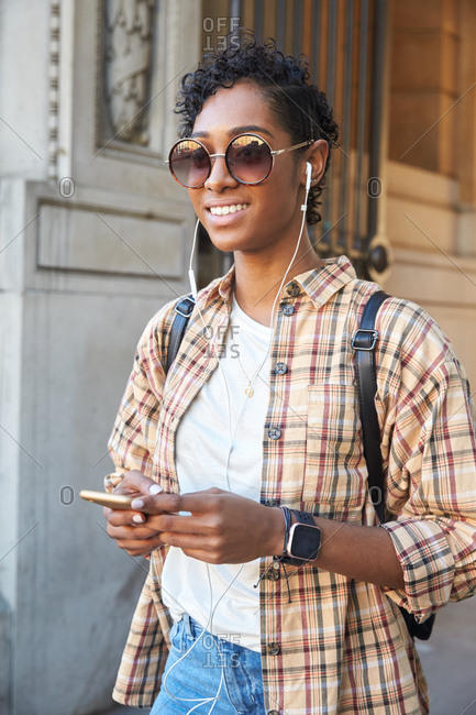 Young woman wearing plaid shirt, sunglasses and earphones standing on the street holding her smartphone, waist up, close up