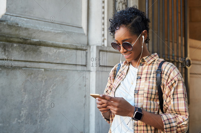 Young woman wearing plaid shirt, sunglasses and earphones standing on the street using her smartphone, waist up, close up