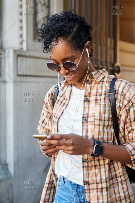 Young woman wearing a plaid shirt and sunglasses standing on a street smiling and using her smartphone, close up