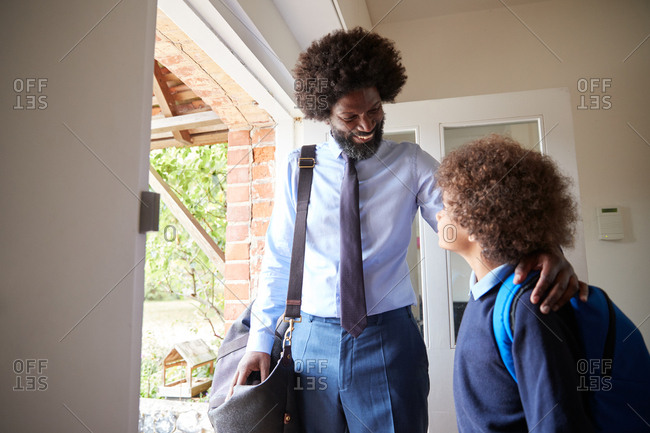 Middle aged man wearing a shirt and tie for work and son wearing school uniform standing in doorway, leaving home together in the morning