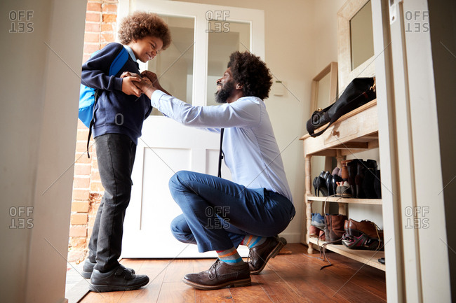 Middle aged man wearing a shirt and tie squatting in the doorway at home preparing his son before he leaves for school in the morning, low angle