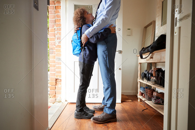 Father in shirt and tie and son in school uniform embracing in the doorway at home, low section, side view