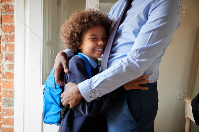 Pre-teen boy wearing school uniform and school bag embracing his father at front door, mid section