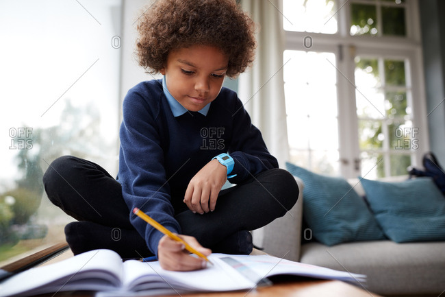 Pre-teen boy wearing school uniform sitting cross legged doing his homework next to window in the living room, close up, selective focus