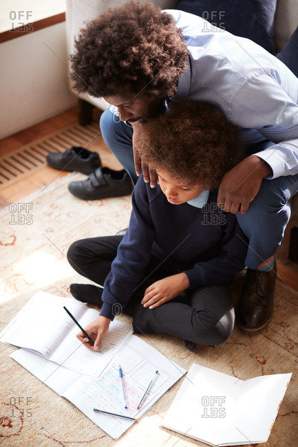 Pre-teen boy in school uniform sitting on the floor at home doing his homework helped by his father, sitting behind him on sofa, elevated view, vertical