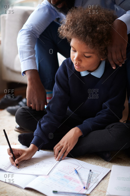 Elevated view of pre-teen boy doing his homework sitting cross legged on the floor in living room and his father helping him, focus on foreground
