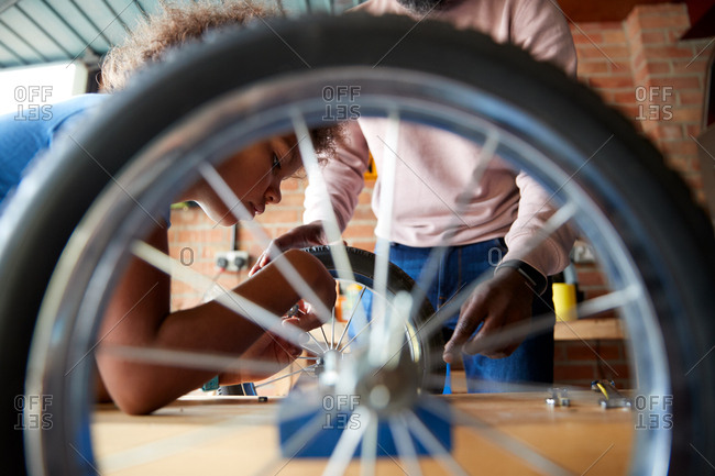 Pre-teen boy building a racing kart with his father in their garage, close up, seen through wheel of kart, selective focus