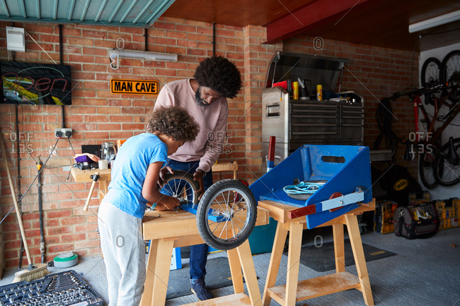 Middle aged father and pre-teen son standing at a workbench building a racing kart together in their garage