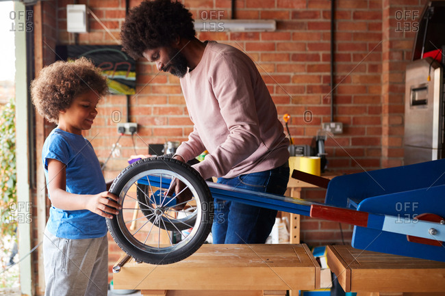 Side view of father and his son making a racing kart together in their garage, standing at workbench