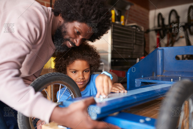 Close up of father helping his son to build a racing kart, standing at workbench in their garage, focus on faces