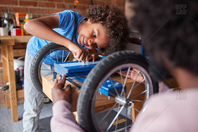 Close up of pre-teen boy working on a go cart, helped by his father, in the foreground, selective focus