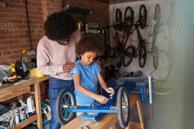 Father and son standing at a workbench making a racing kart together in the garage, seen from open garage door, close up