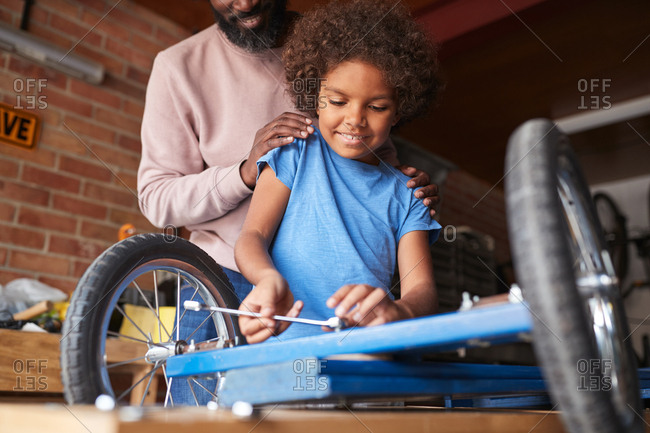Low angle view of pre-teen boy standing at a workbench making a racing kart, with his father standing behind him helping, low angle close up, selective focus