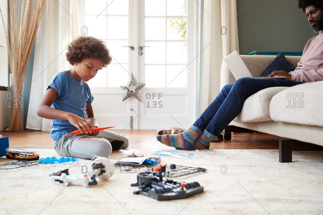 Low angle view of pre-teen boy sitting on the floor playing with a construction kit and his father sitting on a sofa using a laptop in their living room, close up, selective focus, close up