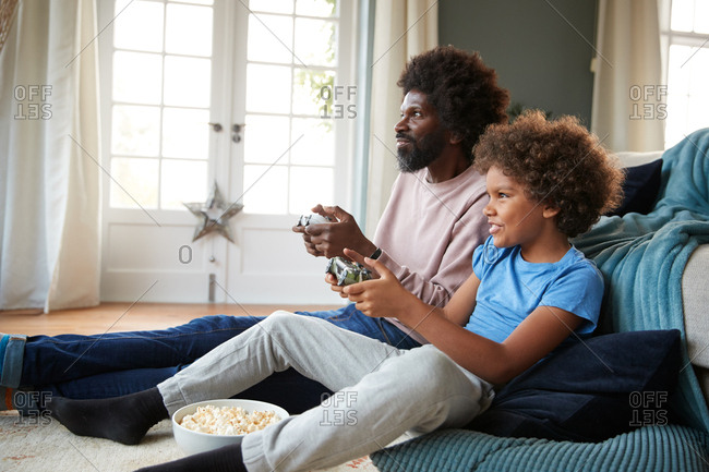 Pre-teen boy and his father sitting on the floor in their sitting room playing video games together, looking up at  screen, side view, close up