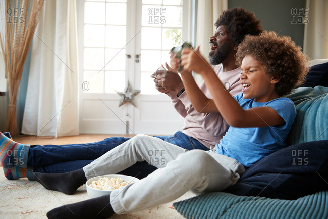 Excited pre-teen boy and his father sitting on the floor leaning on sofa playing video games together, side view