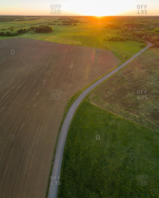 Aerial view of road going through forest in Estonia.