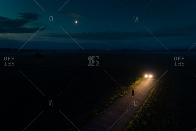 Aerial view of man standing on road at night with waning moon, Estonia