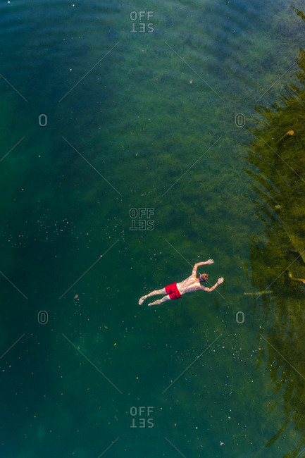 Aerial view of man floating on water at Sinijarv lake in Estonia.