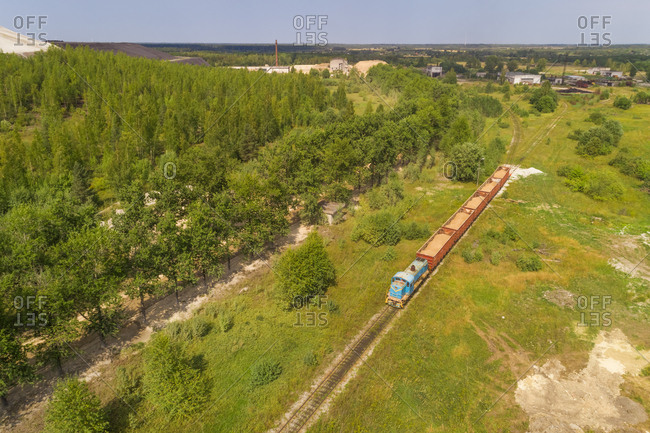 Aerial view of train carrying sand out of factory in Kivioli, Estonia.