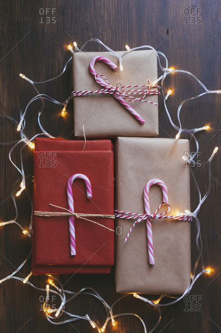 Wrapped Christmas presents with decorations and lights on wooden background