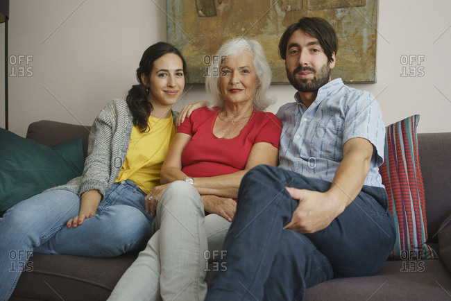 Portrait senior mother sitting with daughter and son on living room sofa