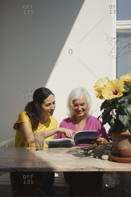 Senior mother and daughter reading magazine on sunny patio