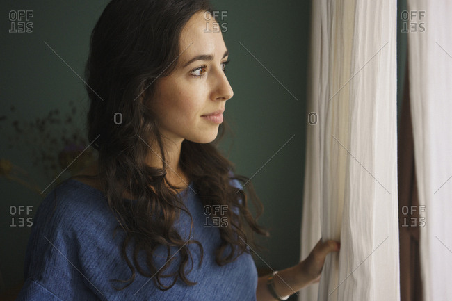 Curious woman standing at window, waiting