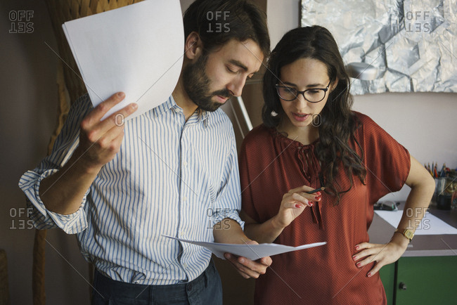 Businessman and businesswoman reviewing paperwork in office