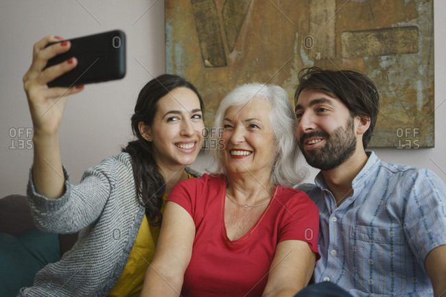 Senior mother taking selfie with daughter and son