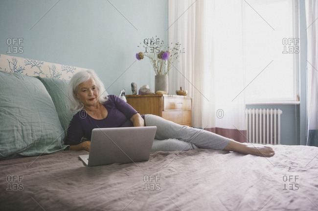 Senior woman using laptop on bed