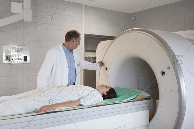 Doctor preparing patient for MRI in hospital