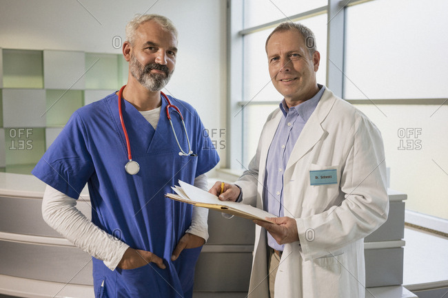 Portrait confident male doctors with medical record in hospital