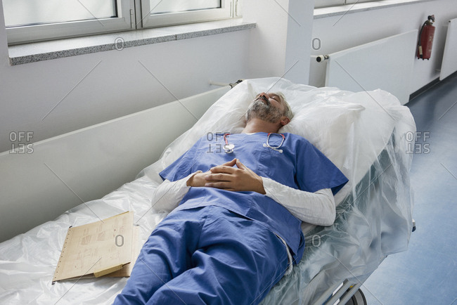 Exhausted doctor resting, sleeping on stretcher in hospital corridor