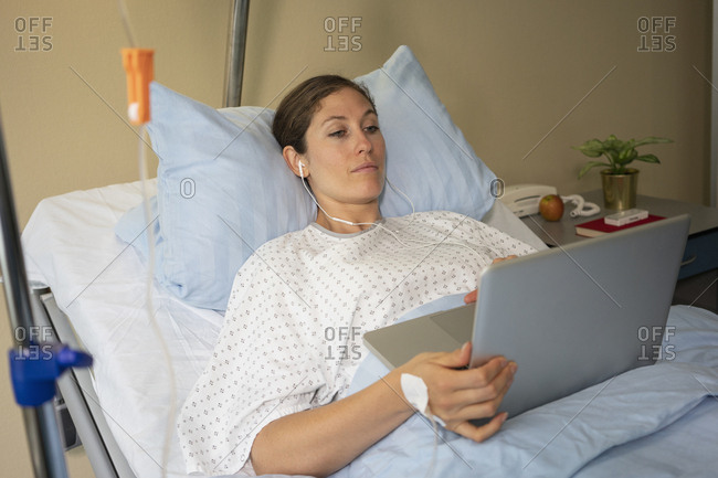 Female patient using laptop, resting and recovering in hospital room