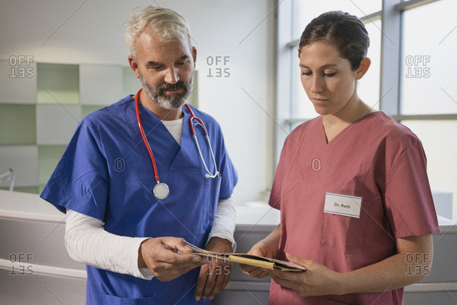 Doctors reviewing medical record in hospital