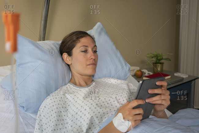 Female patient with digital tablet resting, recovering in hospital bed