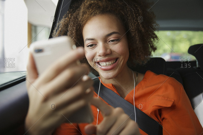 Smiling young woman using smart phone in car