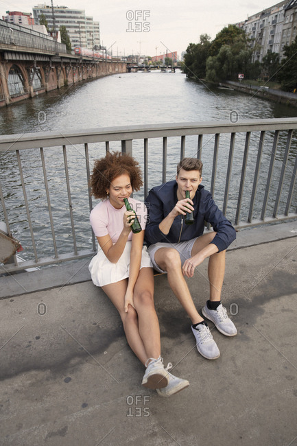 Young couple drinking beer on urban bridge over river